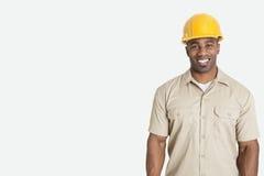 Porträt des glücklichen jungen afrikanischen Mannes, der gelben Schutzhelmsturzhelm über grauem Hintergrund trägt stockfotos