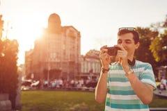 Porträt des glücklichen jungen Mannes, Touristen mit der Kamera, die Fotos der alten Stadt macht Stockbilder