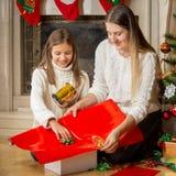 Porträt des glücklichen jungen Mutter- und Tochterverpackung Weihnachtengi Stockfotografie