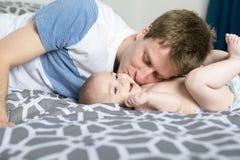Porträt des glücklichen jungen Vaters mit einem Baby im Bett zu Hause lizenzfreie stockfotos