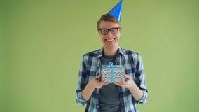 Porträt des glücklichen Kerls im Parteihutholdinggeburtstagsgeschenk und -c$lachen stock video