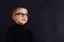 Porträt des glücklichen Kindes im Pullover und in den Gläsern Stockfotos