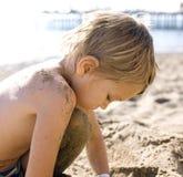 Porträt des glücklichen kleinen Jungen, der auf Strand mit Sand genießt Lizenzfreie Stockbilder