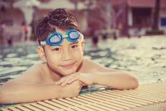 Porträt des glücklichen kleinen Jungen, der im Pool spielt lizenzfreies stockbild