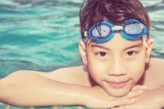 Porträt des glücklichen kleinen Jungen, der im Pool spielt stockbild
