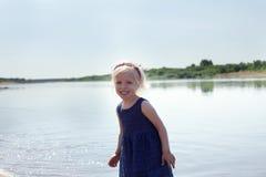 Porträt des glücklichen kleinen Mädchens, das am See stillsteht Stockbild