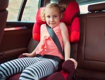 Porträt des glücklichen kleines Kindermädchensitzens bequem in Auto s lizenzfreies stockbild