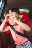 Porträt des glücklichen kleines Kindermädchensitzens bequem in Auto s stockfoto