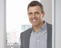 Porträt des glücklichen lächelnden Geschäftsmannes im Büro Stockbild