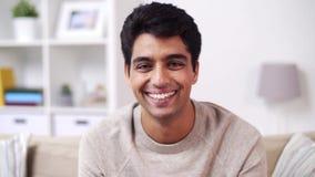Porträt des glücklichen lächelnden jungen indischen Mannes zu Hause stock footage