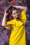 Porträt des glücklichen lächelnden jungen Mädchens im gelben Kleid, das auf Marmor aufwirft, färbte Hintergrund lizenzfreie stockfotografie