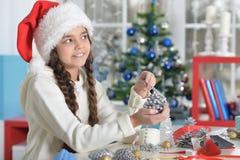 Porträt des glücklichen lächelnden kleinen Mädchens, das für Weihnachten sich vorbereitet lizenzfreies stockbild