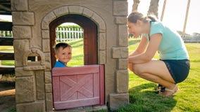 Porträt des glücklichen lächelnden Kleinkindjungen, der im Spielzeugplastikhaus auf dem Kinderspielplatz am Park spielt stockbild