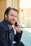 Porträt des glücklichen lächelnden Mannes, der an einem Handy - Stadt spricht Stockfotografie