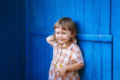 Porträt des glücklichen lächelnden netten kleinen Mädchens gegen die blaue Wand Lizenzfreie Stockfotografie