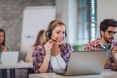 Porträt des glücklichen lächelnden weiblichen Kundenbetreuungs-Telefonbetreibers stockfoto
