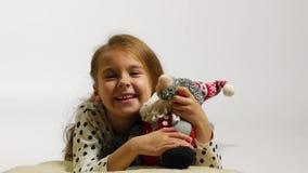 Porträt des glücklichen Mädchens Weihnachtsmann-Spielzeug umarmend Lustiges wellenartig bewegendes hallo des jungen Mädchens stock footage
