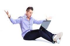 Porträt des glücklichen Mannes arbeitend an Laptop in zufälligem Stockbild