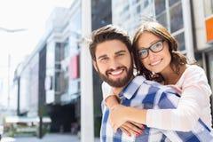 Porträt des glücklichen Mannes Fahrt piggyback gebend der Frau in der Stadt Lizenzfreies Stockbild