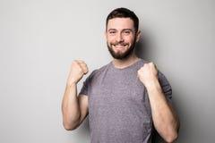 Porträt des glücklichen Mannes steigen oben Hände und erfolgreiche Leistung von Zielen auf Grau lizenzfreie stockfotografie