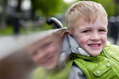Porträt des glücklichen netten lächelnden schönen blonden Jungen, der auf einem Ben sitzt Lizenzfreies Stockbild