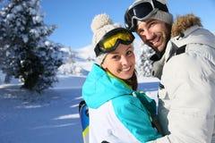 Porträt des glücklichen Paars in den schneebedeckten Bergen Stockfotos