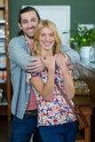 Porträt des glücklichen Paars in einer Kaffeestube umfassend lizenzfreie stockfotografie