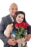Porträt des glücklichen Paars mit Blumen, Kamera betrachtend. stockfotografie