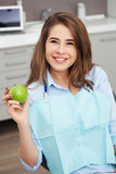 Porträt des glücklichen Patienten im zahnmedizinischen Stuhl mit grünem Apfel stockbilder