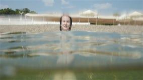 Porträt des glücklichen schönen jungen Mädchens in der Sonnenbrille, die in einer Welle einer Brandung auf kieseligem Beachm, Unt stock footage