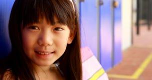 Porträt des glücklichen Schulmädchens sitzend im Umkleideraum 4k stock video footage