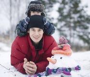 Porträt des glücklichen Vaters mit seinem Sohn draußen mit Schneemann Lizenzfreie Stockfotografie