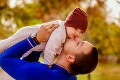 Porträt des glücklichen Vaters und des Babys im Park Stockbild