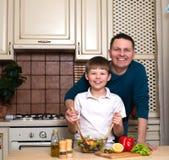 Porträt des glücklichen Vaters und seines des Sohns, die einen Salat in der Küche zubereitet Stockbilder