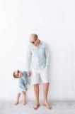 Porträt des glücklichen Vaters und seines kleinen Sohns, auf dem weißen Hintergrund Sie betrachten einander Stockbild