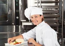 Weiblicher Chef mit Teller am Zähler Stockfotos