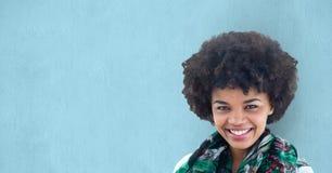 Porträt des glücklichen weiblichen Hippies gegen blauen Hintergrund Stockfotografie