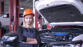 Porträt des glücklichen weiblichen Mechanikers beim Arbeiten in der AutoReparaturwerkstatt nahe Automobil mit offener Haube stock footage