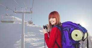 Porträt des glücklichen weiblichen Wanderers, der Kamera auf Schnee hält, bedeckte Berg Lizenzfreies Stockbild
