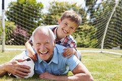 Porträt des Großvaters und des Enkels mit Fußball Stockfotos