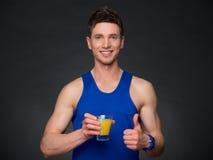 Porträt des gutaussehenden Mannes mit Orangensaft, blaues T-Shirt Lizenzfreies Stockfoto