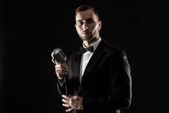 Porträt des gutaussehenden Mannes singen auf Mikrofon auf schwarzem Hintergrund Lizenzfreie Stockbilder