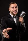 Porträt des gutaussehenden Mannes singen auf Mikrofon auf schwarzem Hintergrund Lizenzfreies Stockbild