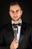 Porträt des gutaussehenden Mannes singen auf Mikrofon auf schwarzem Hintergrund Lizenzfreies Stockfoto