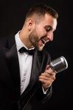 Porträt des gutaussehenden Mannes singen auf Mikrofon auf schwarzem Hintergrund Lizenzfreie Stockfotografie