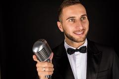 Porträt des gutaussehenden Mannes singen auf Mikrofon auf schwarzem Hintergrund Stockbild