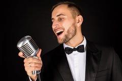 Porträt des gutaussehenden Mannes singen auf Mikrofon auf schwarzem Hintergrund Stockfotografie