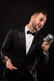 Porträt des gutaussehenden Mannes singen auf Mikrofon auf schwarzem Hintergrund Stockfoto