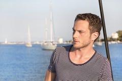 Porträt des gutaussehenden Mannes stehend auf einem Segelboot stockfotografie