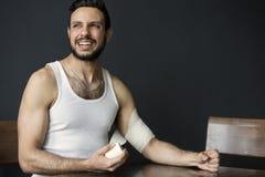 Porträt des gutaussehenden Mannes Verband auf seinen Arm setzend stockfotografie
